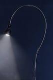 Dark evader. Desk lamp bent into question mark illuminating smoke Royalty Free Stock Image