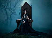 Dark evil queen. Sitting on a luxurious throne,dark boho, cosplay to the film SNOW WHITE AND THE HUNTSMAN ,wild Princess , vampire , hip toning , creative color Royalty Free Stock Photos