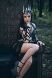 Dark evil queen. Sitting on a luxurious throne, wild Princess , vampire , hip toning , creative color,dark boho stock image