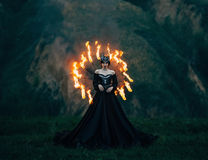 Dark evil queen. Stands on top of a mountain , Lady of fire , vampire, thigh toning , creative color , dark bohemia Stock Photo