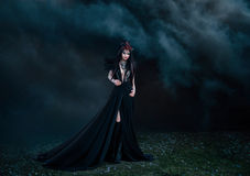 Dark evil queen. Way through the smoke screen of the movie cosplay snow white and the Huntsman wild Princess , vampire , hip toning , creative color,dark boho royalty free stock photo