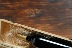 A dark expensive bottle of wine in a wooden box on a wooden background royalty free stock photo