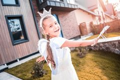 Beautiful dark-eyed girl feeling happy wearing angel costume and little crown stock photos