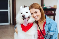 Dark-eyed woman smiling while hugging her cute husky royalty free stock photos