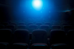 Dark film theater with projection light. And empty seats royalty free stock image