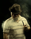 Dark fine art portrait of a smoking man in hat. Royalty Free Stock Photo
