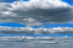 Dark fluffy clouds on background of blue sky Stock Photography