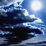 Dark fluffy clouds on background of blue sky Royalty Free Stock Image