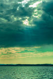 Dark fluffy clouds stormy sky above surface of the sea Stock Images