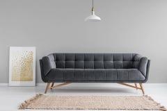 Dark, fluweelbank met houten benen en een beige deken in een minimalistisch woonkamerbinnenland met grijze muren Echte foto royalty-vrije stock foto