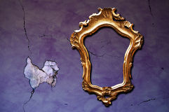 Dark frame. A vintage golden frame on a cracked purple wall Royalty Free Stock Photos