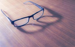 Spectacles on Wooden Surface. Dark-framed reading eyewear on a wooden table, decorated by a less intense shadow and soft light. Slight saturation for a more royalty free stock images