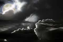 Dark full moon night. Full moon rising in a hole between clouds in dark night Stock Photo