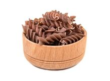 Dark fussili pasta in bowl. Dark raw pasta fusilli in a small wooden bowl on white background Stock Images