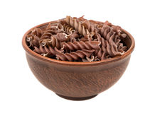 Dark fussili pasta in bowl. Uncooked pasta fussili in a large bowl on white background Stock Photo