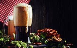 Dark German beer is poured into a glass, fresh green hops and bo royalty free stock images