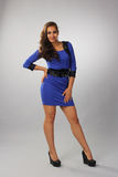 The dark girl with curly hair in a blue dress,full length Stock Images