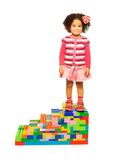 Dark girl standing on toy stairs Royalty Free Stock Photo