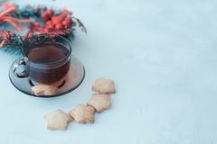 Cup of tea with cookies on a light textural background and a Christmas wreath on the plan. Dark glass cup with a saucer with tea and cookies on a light textural royalty free stock image
