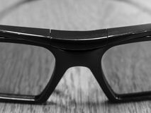 Dark glasses lying on a wooden table stock photography