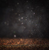Dark glitter vintage lights background. light gold and black. defocused.