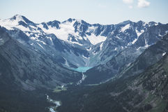 Dark gloom mountain valley along the rapid mountain river. And lake through the stones and rocks on the background of snow peaks and ice glacier, Altai royalty free stock images