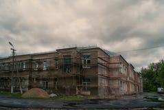 Dark gloomy double-storey house under a cloudy sky Stock Photo