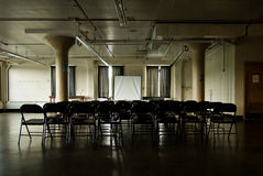 Dark gloomy meeting room. A view of chairs arranged in rows in a large, dimly lighted meeting room Stock Photos