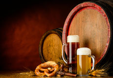 Dark and golden beer. With barrel, brezel and wheat on dark background Stock Image