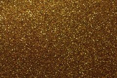 Dark golden sparkling background from small sequins, closeup. Brilliant shiny backdrop from textile. Shimmer bronze paper stock photo