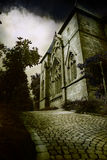 Dark Gothic church. Ancient gothic church at the end of cobblestones road Royalty Free Stock Photography