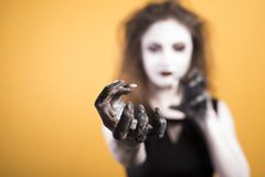Dark gothic young woman in witch halloween costume with makeup and hanf over yellow background royalty free stock photo