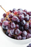 Dark grape in a bowl on white Stock Images