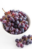 Dark grape in a bowl on white Royalty Free Stock Images