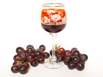 Dark grapes and a glass of wine. On a white background Stock Images