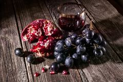 Dark grapes and red wine in a glass stock image