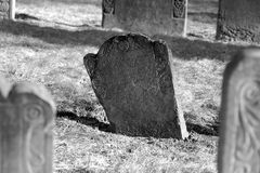 A dark grave. A dark stone stands out in this scene of ancient grave stones in black and white in bright sun light on a beautiful winter's day Royalty Free Stock Images
