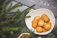 On a dark gray background, fresh spruce branches decorated with dried orange slice and sesame biscuits in a white bowl stock images