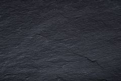 Dark gray black slate background or texture of natural stone. Black board for serving close-up stock image