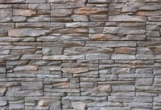 Dark gray and brown exterior wall cladding made of irregular natural stones. Stone paneling, royalty free stock photos
