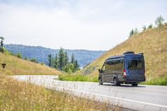 Dark gray compact commercial mini van running on the winding road between the hills. Compact luxury commercial transportation economical, convenient minivan for royalty free stock photography