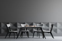 Gray dining room interior, wooden chairs. Dark gray dining room interior with a concrete floor, dark gray and patterned walls, and a dark wooden and white table Royalty Free Stock Photography