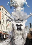 Dark gray mask and white clothes Venice Carnival 2019. Above the mask we see something that looks like horns.And the very top of the mask is to white flowers stock image
