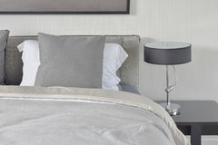 Dark gray pillow with comfy bed and black shade reading lamp.  Stock Image