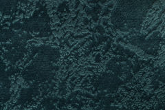 Dark green background from a soft upholstery textile material, closeup. Turqioise spotted fabric with natural texture. Cloth backdrop Stock Photos