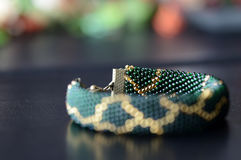 Dark green beaded bracelet with a golden pattern. On a dark background Stock Images