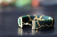 Dark green beaded bracelet with a golden pattern. On a dark background Stock Photo