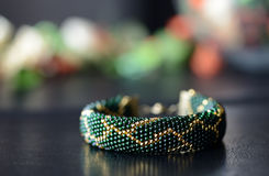 Dark green beaded bracelet with a golden pattern. On a dark background Royalty Free Stock Photos