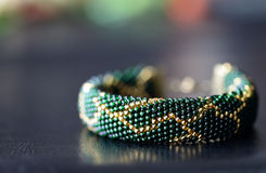 Dark green beaded bracelet with a golden pattern. On a dark background Royalty Free Stock Images