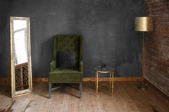 Dark green soft armchair near plaster wall. Arm-chair with fabric upholstery and big vintage mirror in loft style interior royalty free stock images